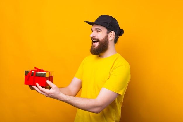 Um homem feliz dando um presente sorrindo perto de uma parede amarela