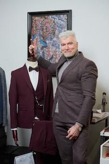 Um homem feliz e maduro com cabelos grisalhos e um físico esportivo está brincando perto de um manequim em uma loja de roupas. um cliente do sexo masculino com barba usa terno em uma boutique.