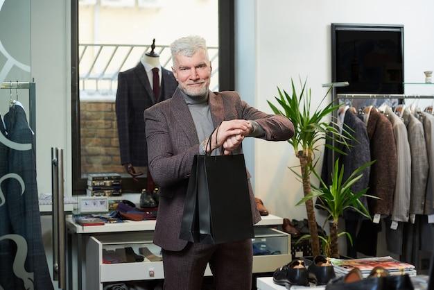 Um homem feliz e maduro com cabelos grisalhos e um físico esportivo está olhando para seu relógio de pulso segurando duas sacolas de papel preto em uma loja de roupas. um cliente do sexo masculino com barba usa um terno de lã em uma boutique