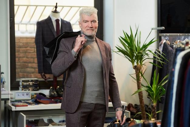 Um homem feliz e maduro com cabelos grisalhos e um físico esportivo jogou duas sacolas de papel preto nas costas com as compras em uma loja de roupas. um cliente do sexo masculino com barba usa um terno de lã em uma boutique