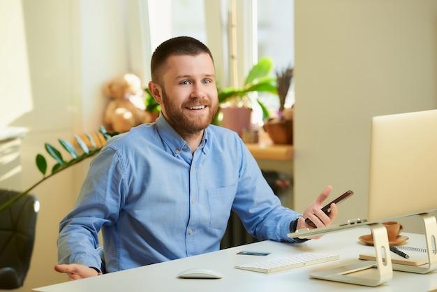 Um homem feliz em ouvir seus colegas em uma entrevista on-line em seu apartamento.