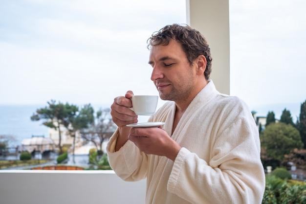 Um homem feliz em um roupão branco está desfrutando de uma xícara de café ou chá da manhã em pé em uma varanda com vista para o mar. o conceito de relaxamento e estilo de vida saudável