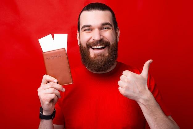 Um homem feliz está segurando um passaporte com duas passagens e mostrando um polegar para cima