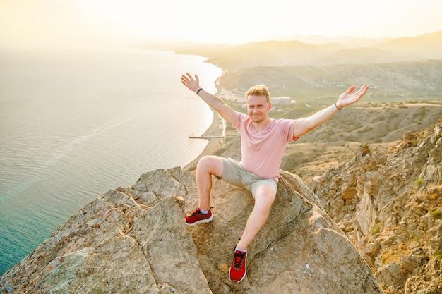 Um homem feliz está sentado com as mãos abertas na beira de um penhasco acima do mar
