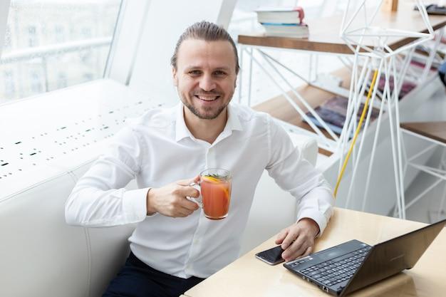 Um homem feliz que senta-se na tabela que guarda um copo da bebida em seguida a janela no interior moderno branco.