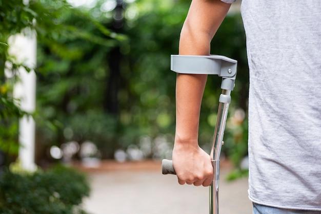 Um homem ferido tenta andar de muletas no parque em um fundo desfocado