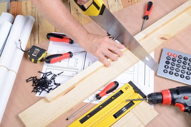Um homem fez um móvel com várias ferramentas de carpintaria