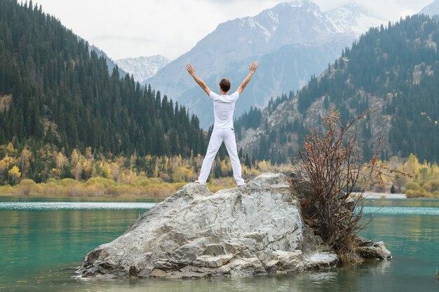 Um homem fica de pé em uma grande pedra e levanta as mãos para o céu picos nevados das montanhas