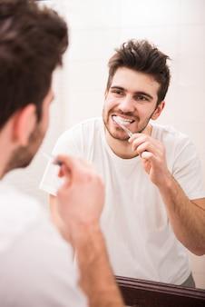 Um homem fica na frente do espelho e escova os dentes.