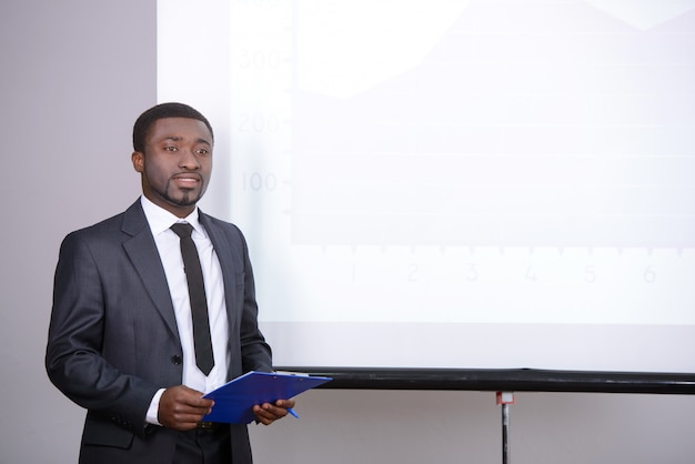 Um homem fica perto da placa e mostra uma apresentação.