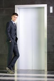 Um homem fica perto do elevador e olha para a câmera.