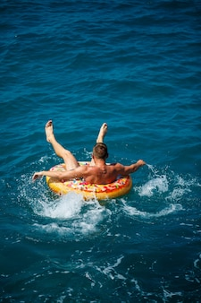 Um homem flutua em um anel inflável no mar com água azul. férias no mar em um dia ensolarado. conceito de férias na turquia. foco seletivo