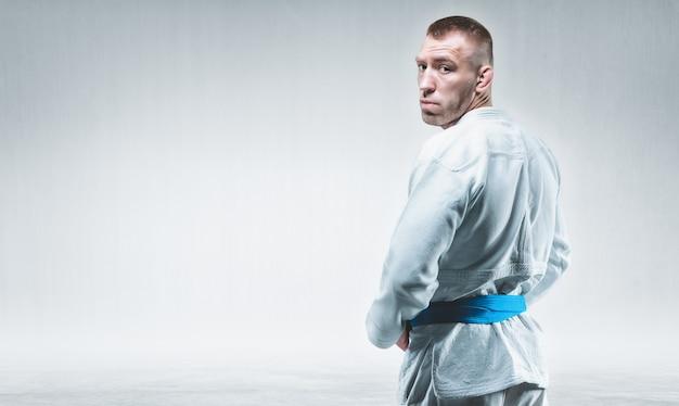 Um homem forte de quimono olha por cima do ombro. conceito de caratê, sambo, jiu-jitsu. mídia mista