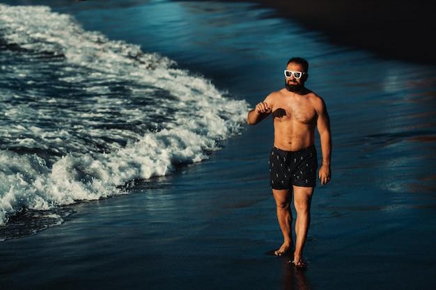 Um homem forte de short preto e óculos caminha pela praia de areia vulcânica negra na ilha de tenerife. espanha.