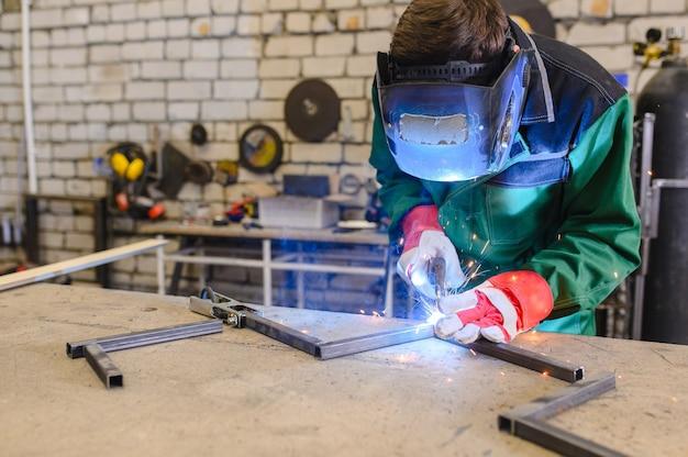 Um homem forte é um soldador com uma máscara de soldagem e solda couro, um produto de metal é soldado com uma máquina de soldar na garagem