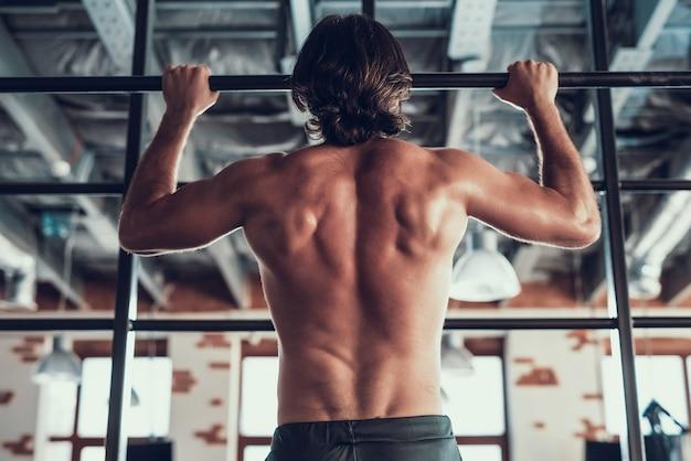 Um homem forte executa pull-ups na barra.