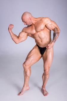 Um homem forte mostra o bíceps.