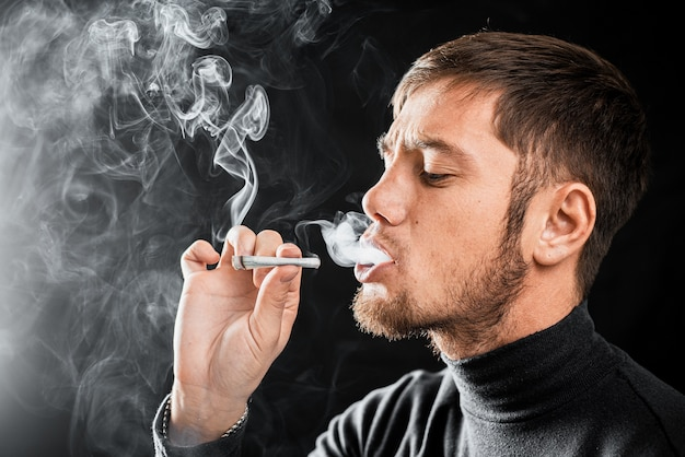 Um homem fuma um cigarro com uma nota de dinheiro enrolada