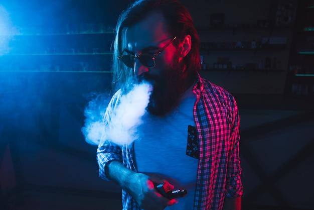 Um homem fuma um cigarro e solta fumaça em uma boate.