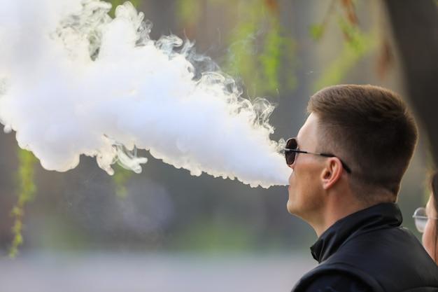 Um homem fuma um cigarro eletrônico e sopra a fumaça