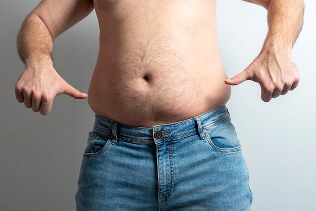 Um homem gordo de jeans com a barriga descoberta mostra os polegares para baixo com as duas mãos.