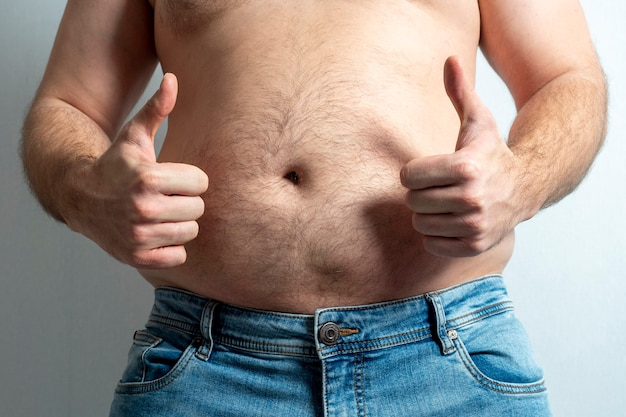 Um homem gordo de jeans com a barriga nua e um dedo levantado no ar. o conceito de positividade corporal. auto aceitação