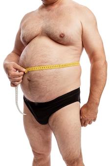 Um homem gordo de short mede o volume do abdômen. isolado. fechar-se.