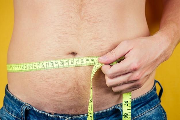 Um homem gordo e uma fita métrica na barriga. conceito de nutrição pouco saudável.
