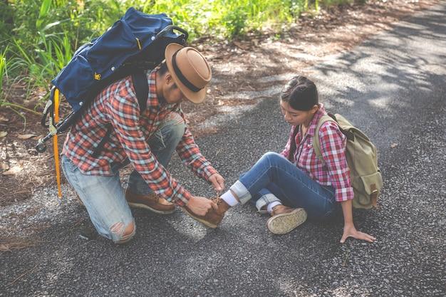 Um homem gosta de amarrar seus sapatos para sua namorada durante a caminhada, escalada.