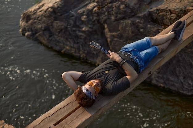 Um homem hippie com óculos e um lenço na cabeça está deitado em uma ponte de madeira sobre o rio e ...