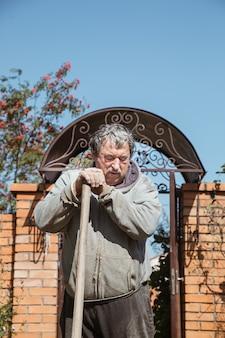 Um homem idoso apoiou-se no cabo de uma pá para um breve descanso entre o trabalho em sua casa de verão