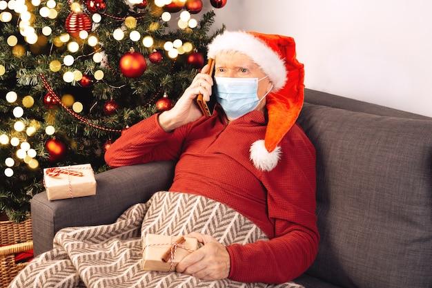Um homem idoso, caucasiano, com um chapéu de papai noel e uma máscara médica fala ao telefone, sentado em um sofá perto de uma árvore de natal. auto-isolamento, coronavírus, clima de férias. caixas de presente.