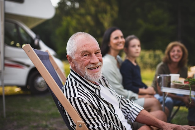 Um homem idoso com uma família de várias gerações sentado em um carro e olhando para uma caravana de câmera na viagem de férias
