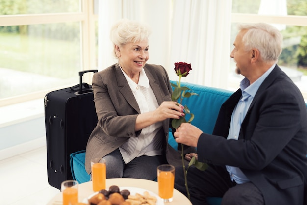 Um homem idoso dá uma rosa para uma mulher idosa