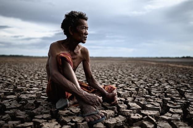 Um homem idoso estava sentado abraçando os joelhos dobrados em solo seco e olhando para o céu