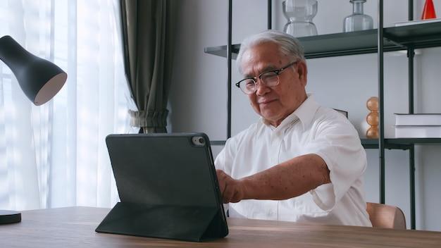Um homem idoso lendo notícias com o tablet na mesa em casa. um velho asiático procura informações na internet enquanto está sentado a uma mesa.
