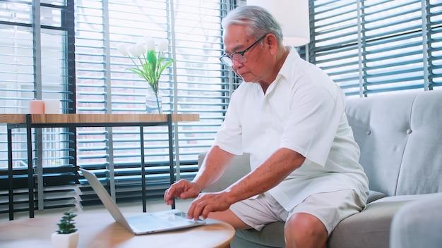 Um homem idoso lendo notícias com o tablet no sofá em casa. um idoso asiático procura informações na internet enquanto está sentado na sala de estar