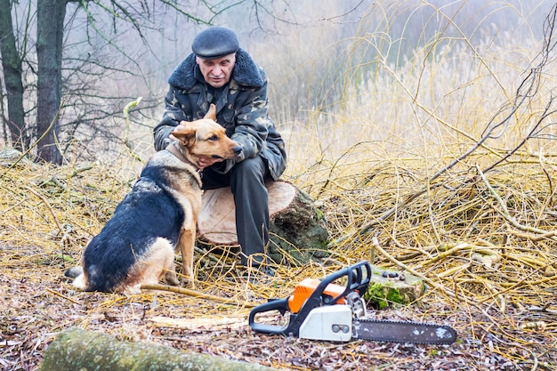 Um homem idoso na natureza se comunica com um cachorro