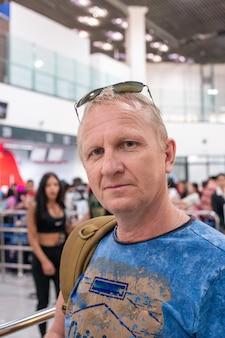 Um homem idoso no aeroporto está fazendo check-in para um voo