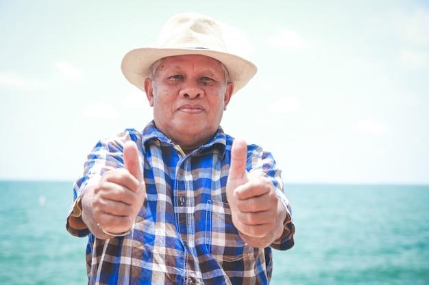 Um homem idoso, polegares para cima, boa saúde, vem à praia, relaxa