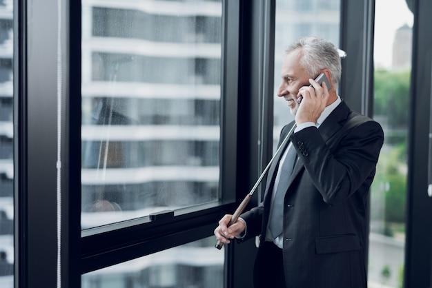 Um homem idoso respeitável que joga um mini golfe no escritório.