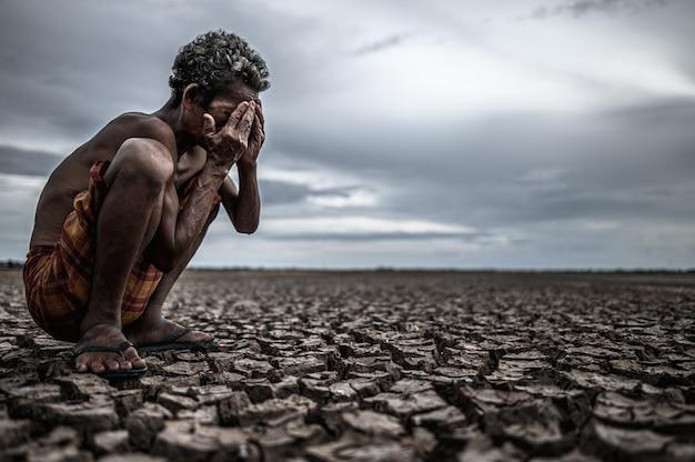 Um homem idoso sentado dobrou os joelhos em solo seco e as mãos fechadas no rosto, aquecimento global