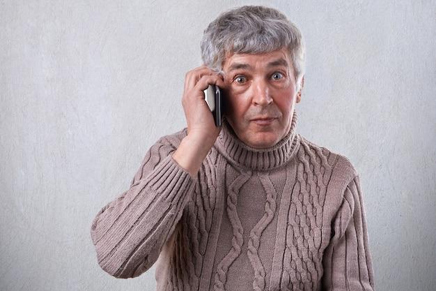 Um homem idoso surpreso na camisola com cabelos grisalhos, olhos escuros e rugas no rosto, comunicando-se por telefone