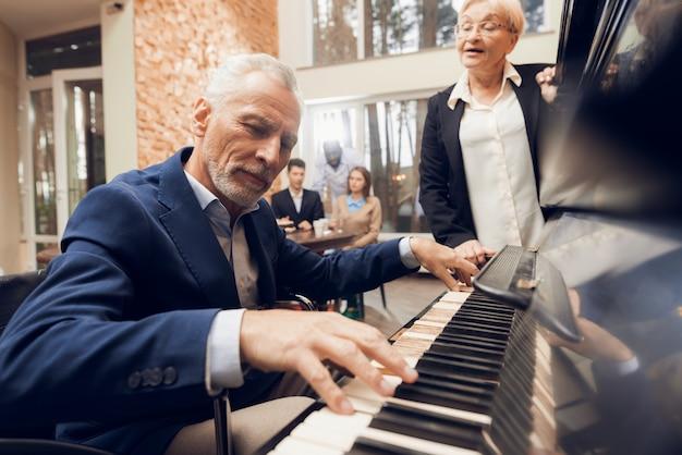 Um homem idoso toca piano em um lar de idosos.