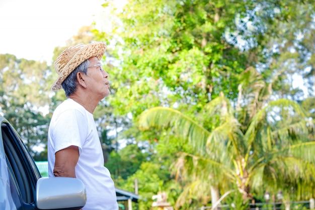 Um homem idoso usando um chapéu de cowboy, vestindo uma camisa branca, encostado em um carro, esperando para ir em uma viagem.