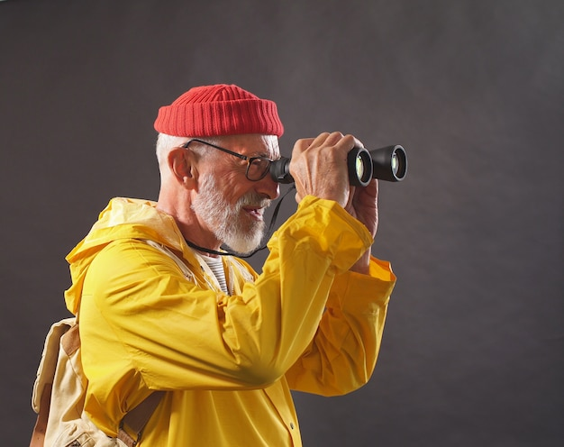Um homem incrível, um homem de boné vermelho e uma capa de chuva amarela brilhante aprecia a vista de smortya à distância usando binóculos, fundo isolado. passatempo