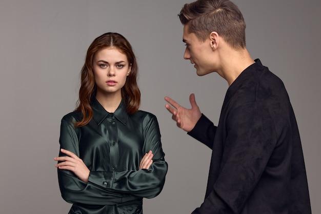 Um homem indignado com uma jaqueta preta gesticula com as mãos e olha para a mulher.