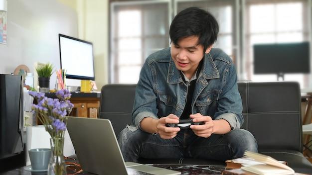 Um homem inteligente está jogando videogame e sentado em frente ao seu computador laptop no sofá de couro.