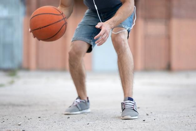 Um homem joga basquete no quintal da rua durante o dia