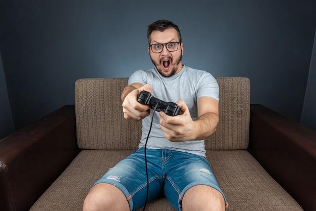 Um homem joga o console, os videogames reagem forte e emocionalmente enquanto está sentado no sofá. dia de folga, entretenimento, lazer.